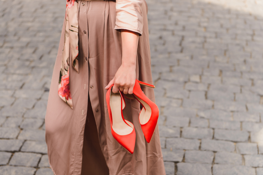 Frau mit roten High Heels in der Hand