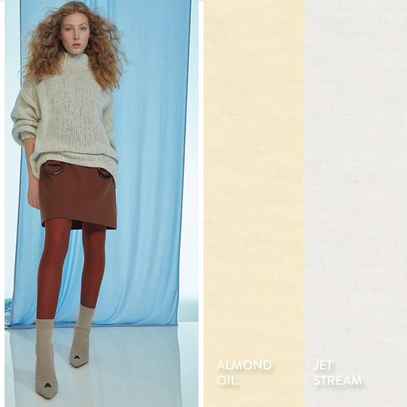 Model trägt offwhite Strickpullover über braunem Sixtieskleid