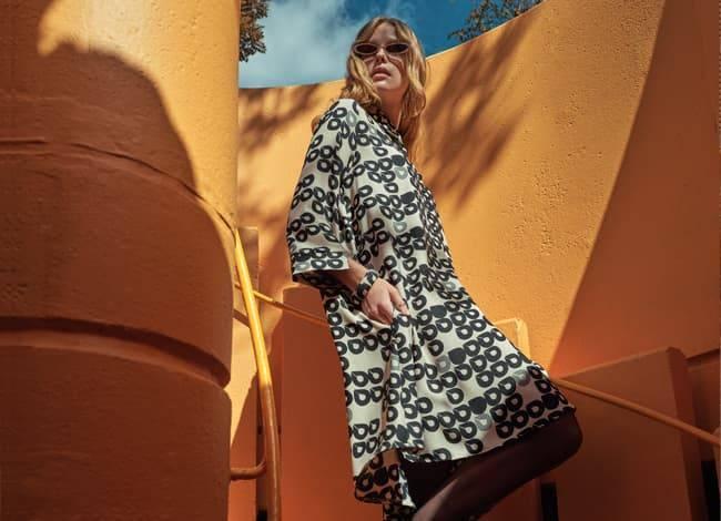 Model wears a wide Blouse Dress with Logoprint