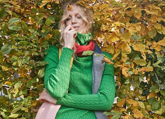 Model trägt grünen Strickpullover Biane und bunten Fransenschal