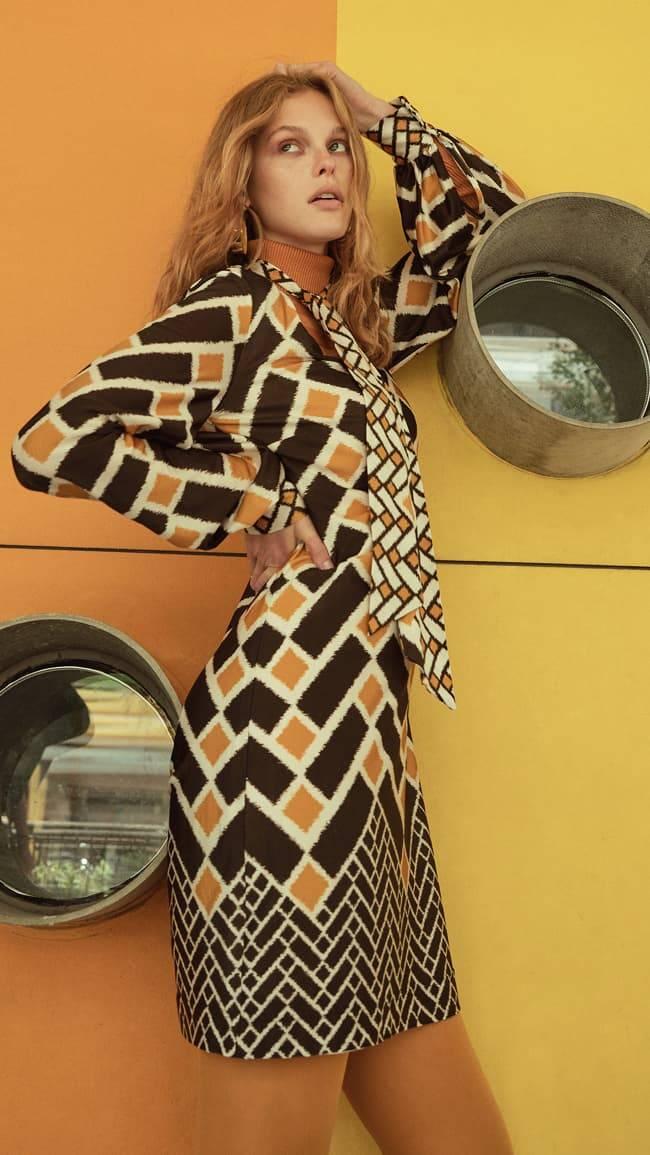 Model wears yellow-checked print dress