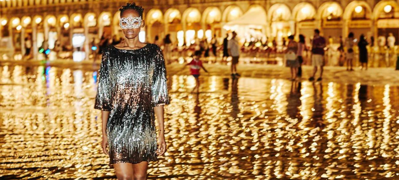 Model trägt gold-schwarzes Abendkleid in Venedig