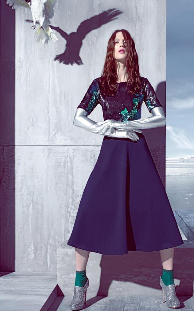 Model mit Paillettentop und blauem Rock in Eislandschaft
