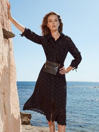 Model in schwarzem Blusenkleid mit Lockstickerei