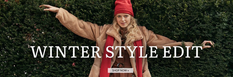 Model trägt roten Strickschal und beigen Kunstfellmantel