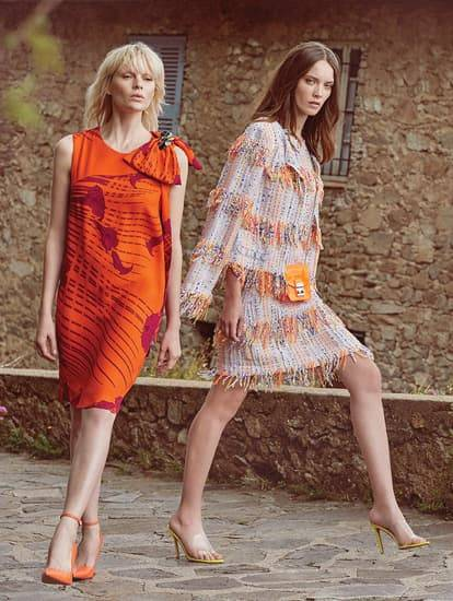 Ein Model trägt ein knall-oranges A-Linien Kleid. Ein weiteres Model trägt ein Kostüm im Fransenlook.
