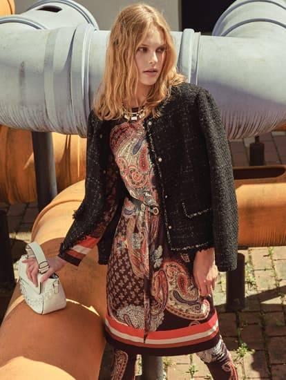 Model Herbstkleid im Paisleymuster und Boucle-Jacke in gedeckten Farben