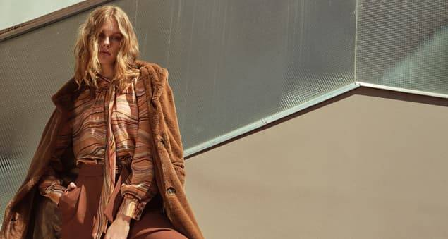 Model trägt braunen Kunstfellmantel mit abgestimmter Bluse im Herbstlook