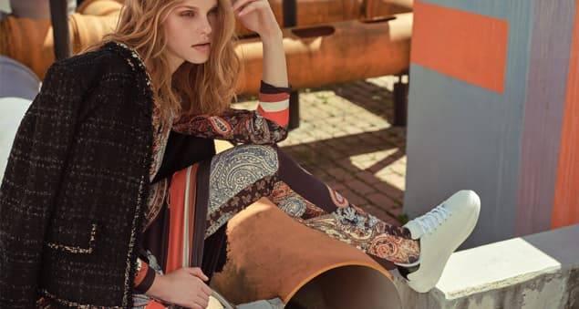 Model trägt Kleid über Leggings im Paisleyprint sowie Boucle-Jacke im Layering Look