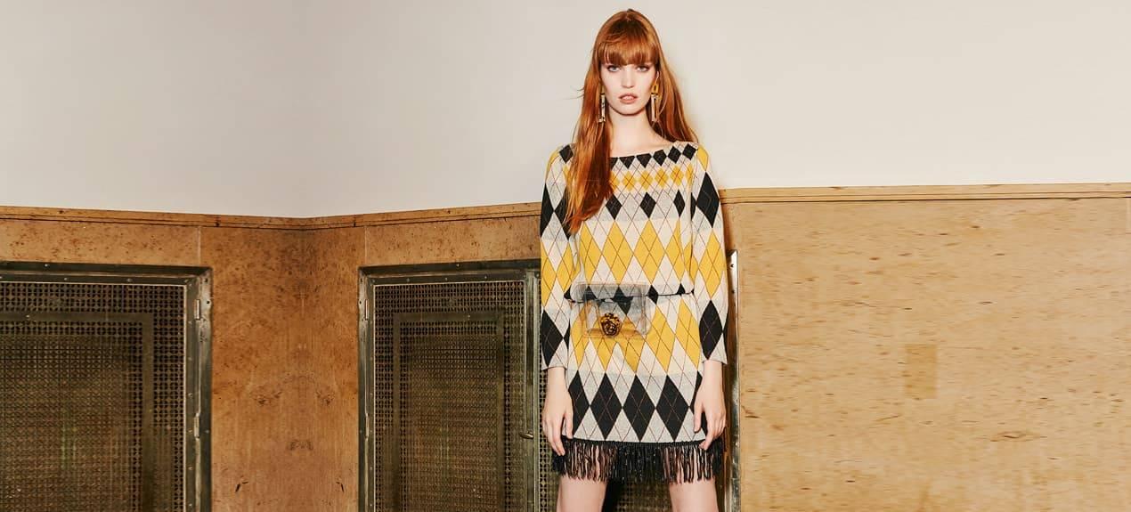 Model trägt scharz-gelbes Karokleid mit Fransen und Gürteltasche
