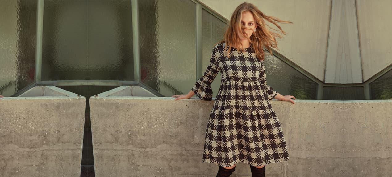 Model trägt kaschierendes Tunikakleid mit Karomuster in Schwarz-Grau