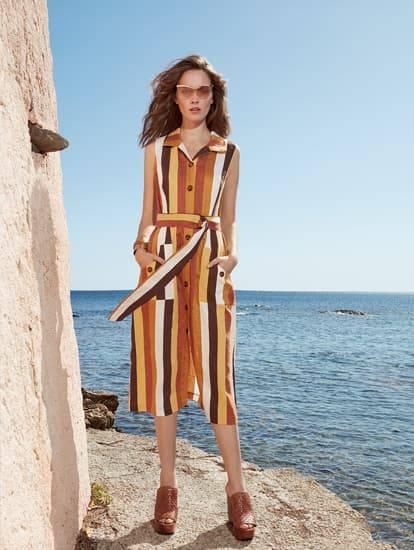Model trägt Leinenkleid in Midi mit Blockstreifen