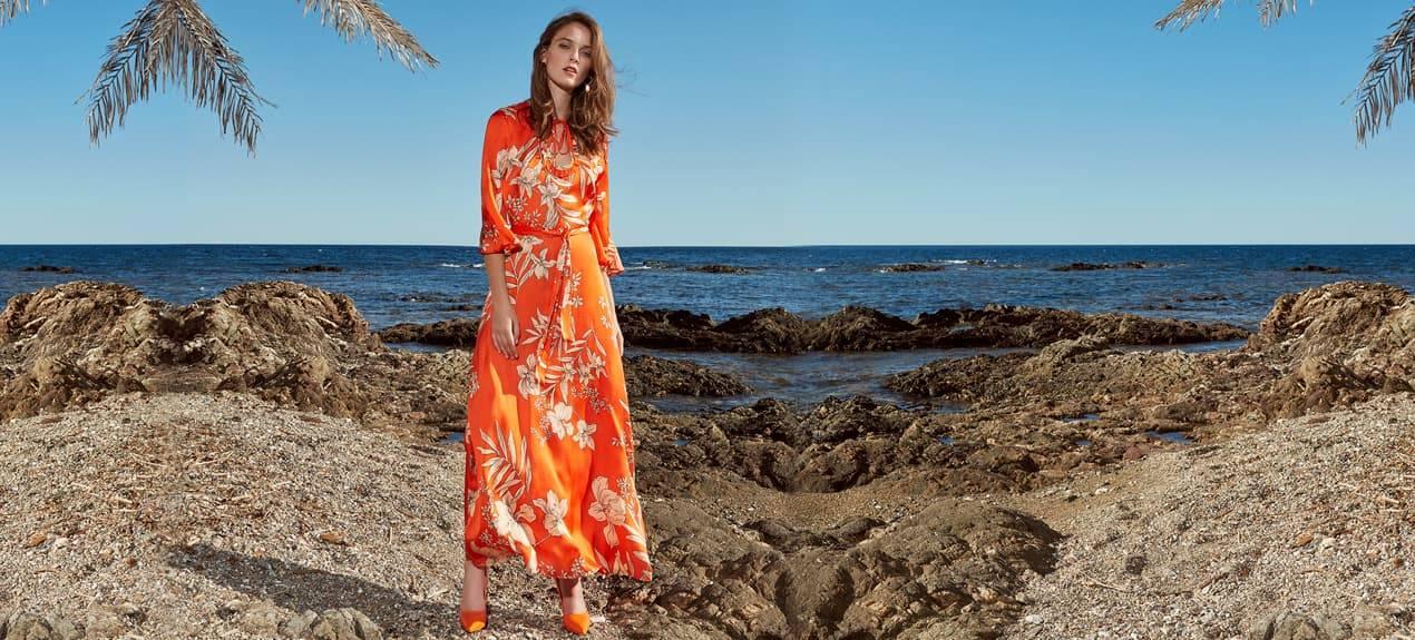 Model trägt orange-farbenes Midikleid mit Blütenprint an der Cote d´Azur
