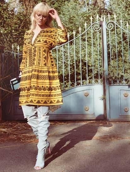 Model trägt ockerfarbenes Baumwollkleid mit Ethnostickerei