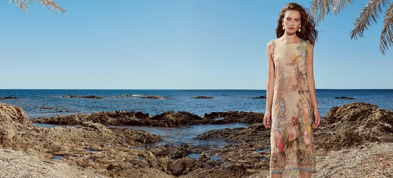 Model trägt pastellfarbenes Kleid am Strand