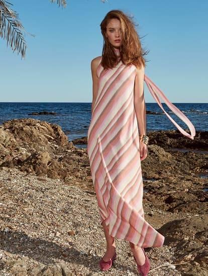 Model trägt rosa gestreiftes Maxikleid an der Cote d´Azur