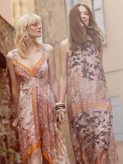 Zwei Models tragen Seidenkleider und flanieren in einer französischen Kleinstadt
