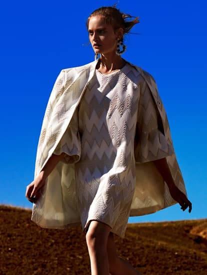 Model trägt weißes Sommerkleid mit Mantel