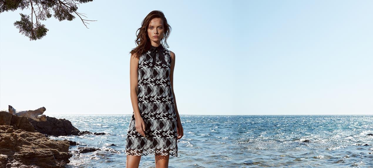 Model trägt schwarz-weißes Spitzenkleid in A-Linie mit dekorativem Kragen
