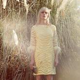 Model trägt gelbes Tunikakleid mit Federn an den Ärmeln